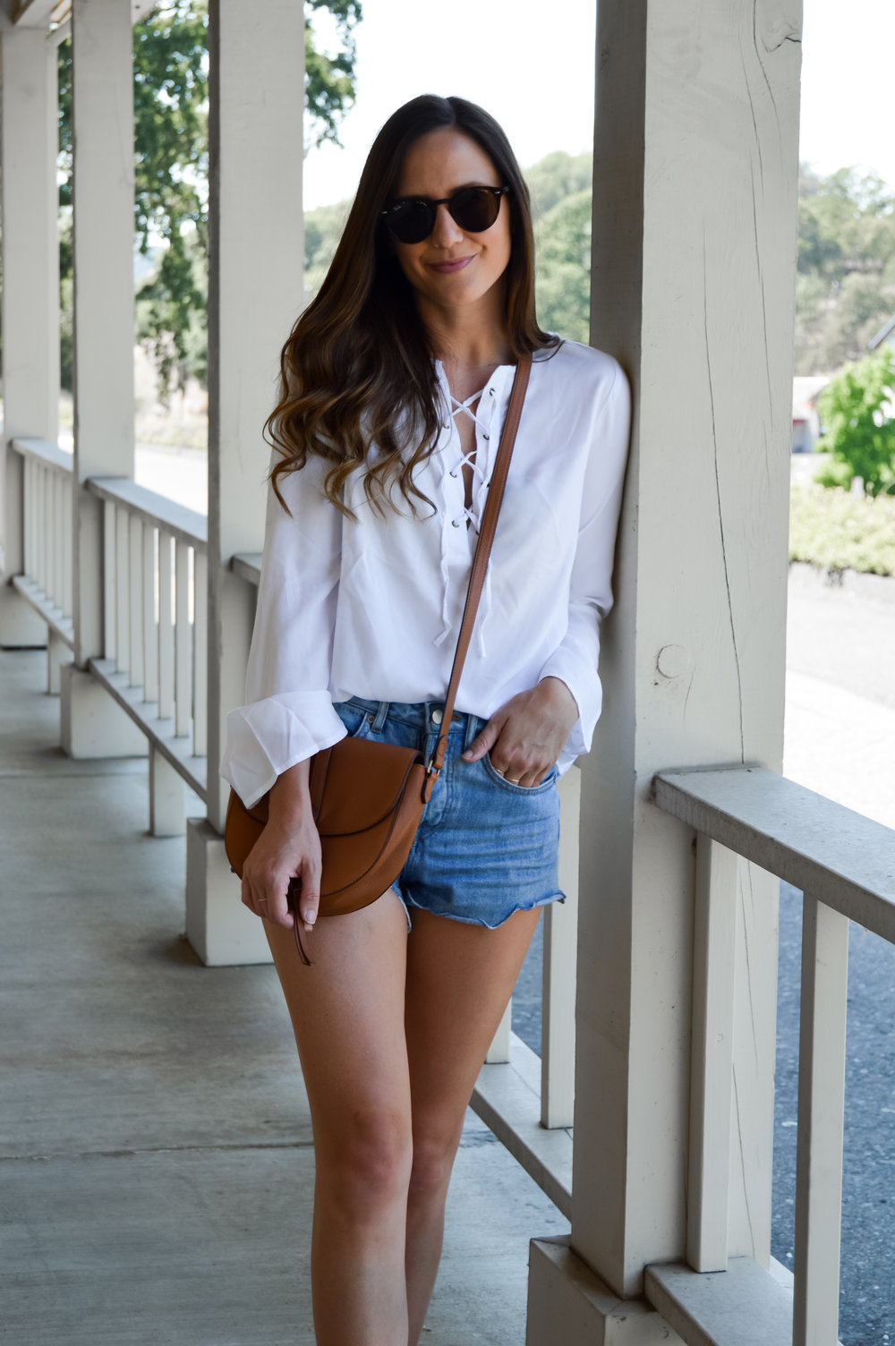 White lace up tunic top tucked into shorts