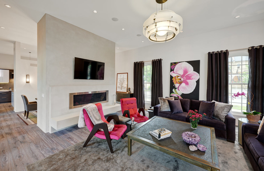Fort Sheridan Ranch - Family Room   Flanked by large windows. Plum velvet sofas and fuschia mid century chairs. The coffee table is steel with a honed granite insert and accessorized with an amethyst crystal bowl.  Featured COUEF pieces:  Madison Classic Ottoman ,  Clark Throw ,  Rex Toss Pillows