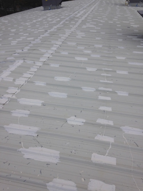 Sealing process in progress, fasteners sealed on a exposed fastener, screw down roof.