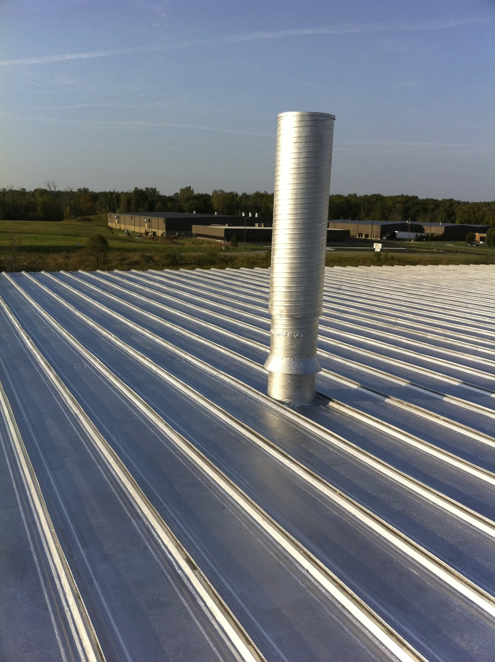 Aluminum metal roof coating for this standing seam metal roof.  Prior to the sealing and coating process there was a leak at this roof pipe, it was sealed prior to coating to stop metal roof leaks