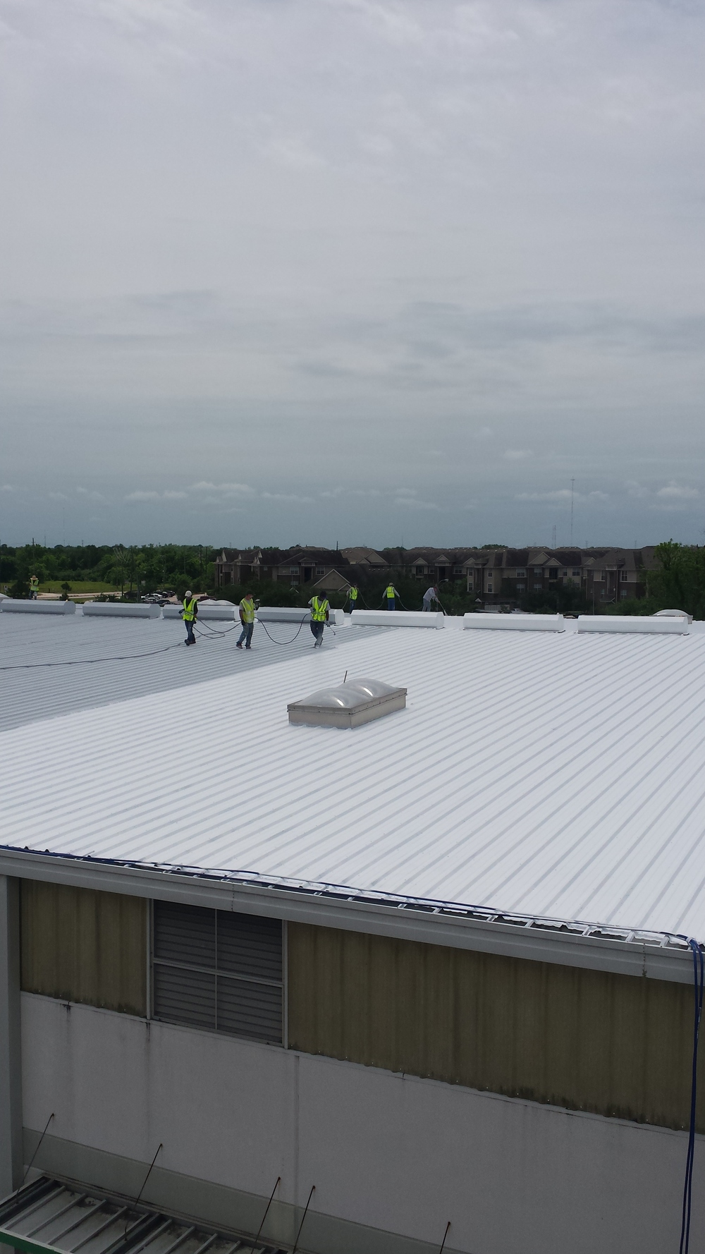 Metal roof coating in process.  White elastomeric roof coating.