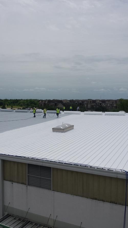 Metal roof coating in process. White elastomeric roof coating.