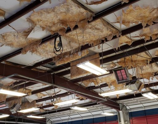 Metal building insulation repair. This is a picture of the ceiling of a service area of an auto dealership. Completed January, 2019