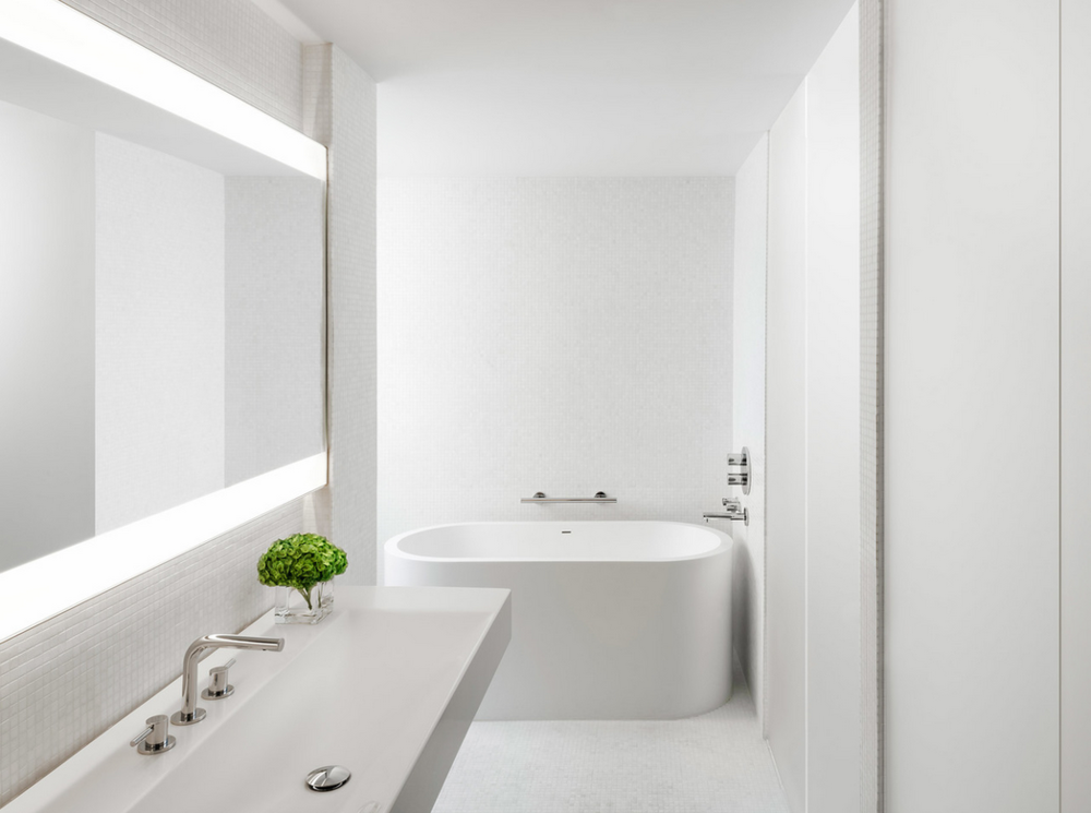 Sleek, ultra modern bathroom. Freestanding tub, floating white vanity.