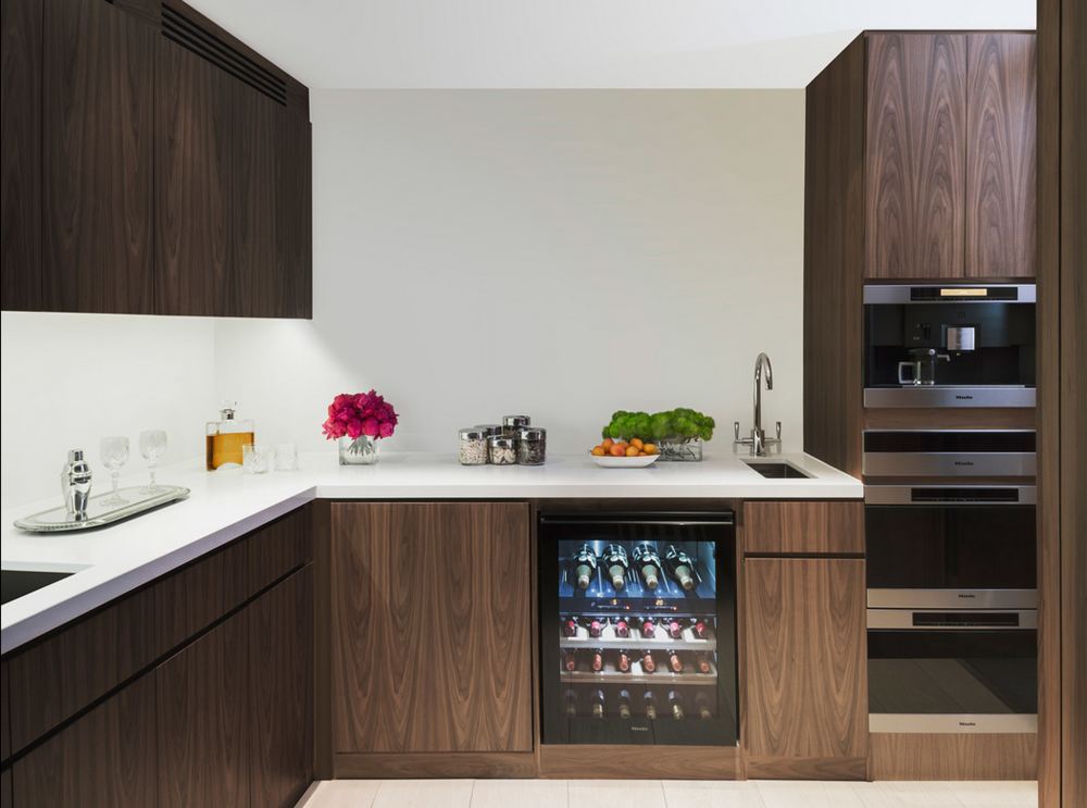 Dark wood in the kitchen, wine fridge, sleek white counters, Miele Appliances.