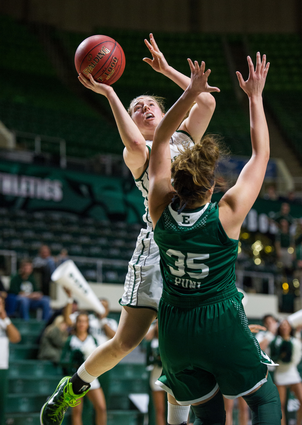 Ohio University sophomore Hannah Boesinger, of Hudson, Ohio, jumps up to the basket to score for the Bobcats amidst the guarding tactics of Eastern Michigan senior Brianna Puni, of St. Charles, Missouri. The Bobcats lost the game 73-61 at the Convocation Center in Athens, Ohio, on February 18, 2015.