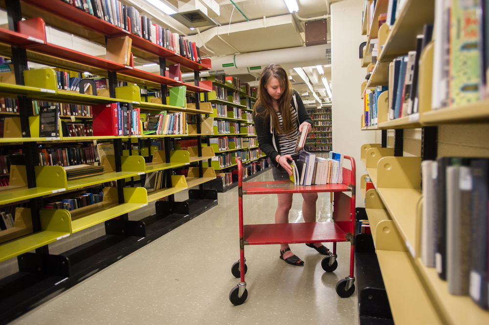 "Chelsea Langlois, a fifth year Ohio University student studying actuarial science, organizes books in ""The Stacks"" of Alden Library in Athens, Ohio, on April 6, 2015."