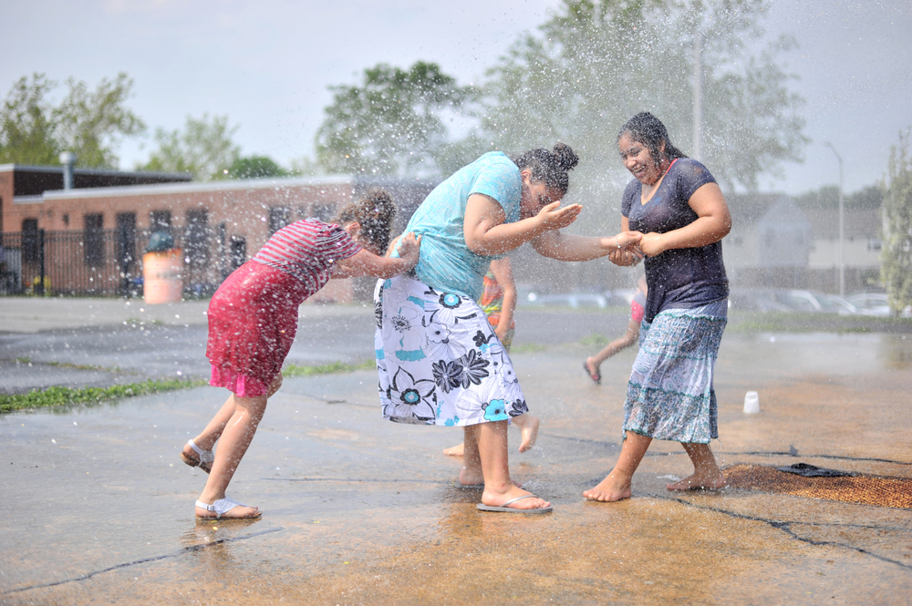 Jailissa Cruz (left), 8, and Ashley Vega (right), 14, try to pull Nayeli Vega (middle), 14, into the water at the splash pad at Yarnell Park on May 26, 2016, in Reading, PA. (Reading Eagle: Sarah Stier)