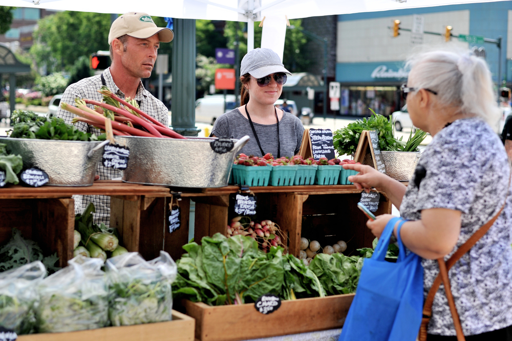 Aida Ruic, of Reading, PA, stops at Oak Nut Farm's booth, manned by Shelby Pritchard and Sean McDermott, at the Penn Street Market in Reading, PA, on June 2, 2016. (Reading Eagle: Sarah Stier)