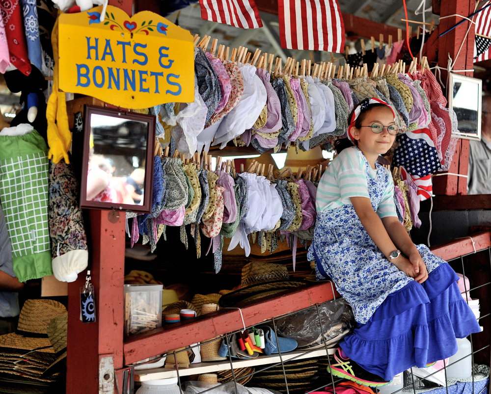 Journey Neulight, 10, of Venice, California, waits for a customer at her grandmother's booth at the Kutztown Folk Festival in Kutztown, PA, on July 4, 2016. (Reading Eagle: Sarah Stier)
