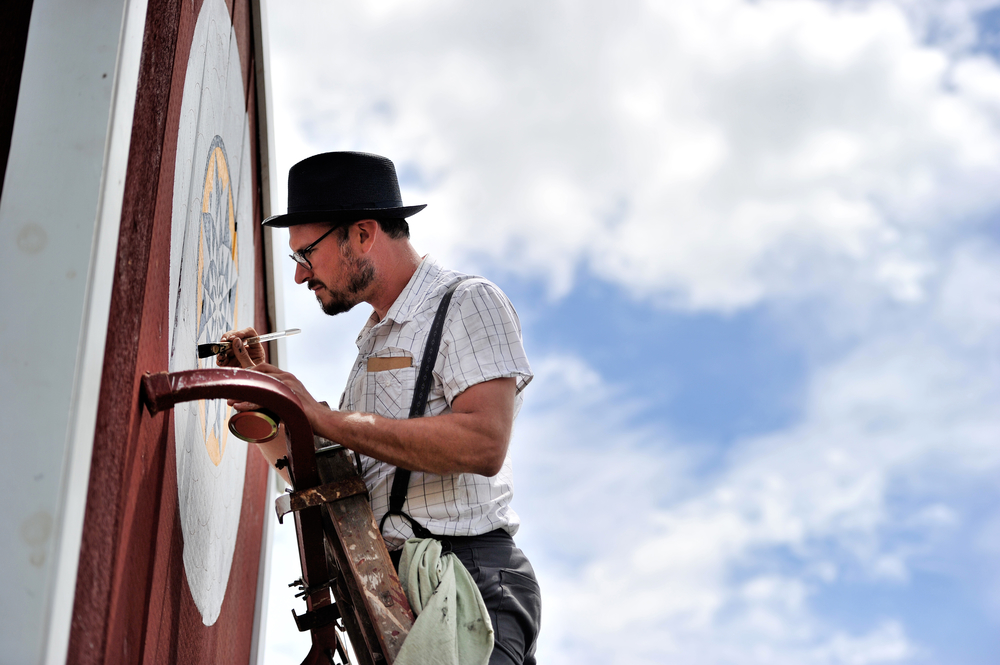 Patrick Donmoyer of Kutztown paints barn stars at the Kutztown Folk Festival in Kutztown, PA, on July 2, 2016. (Reading Eagle: Sarah Stier)