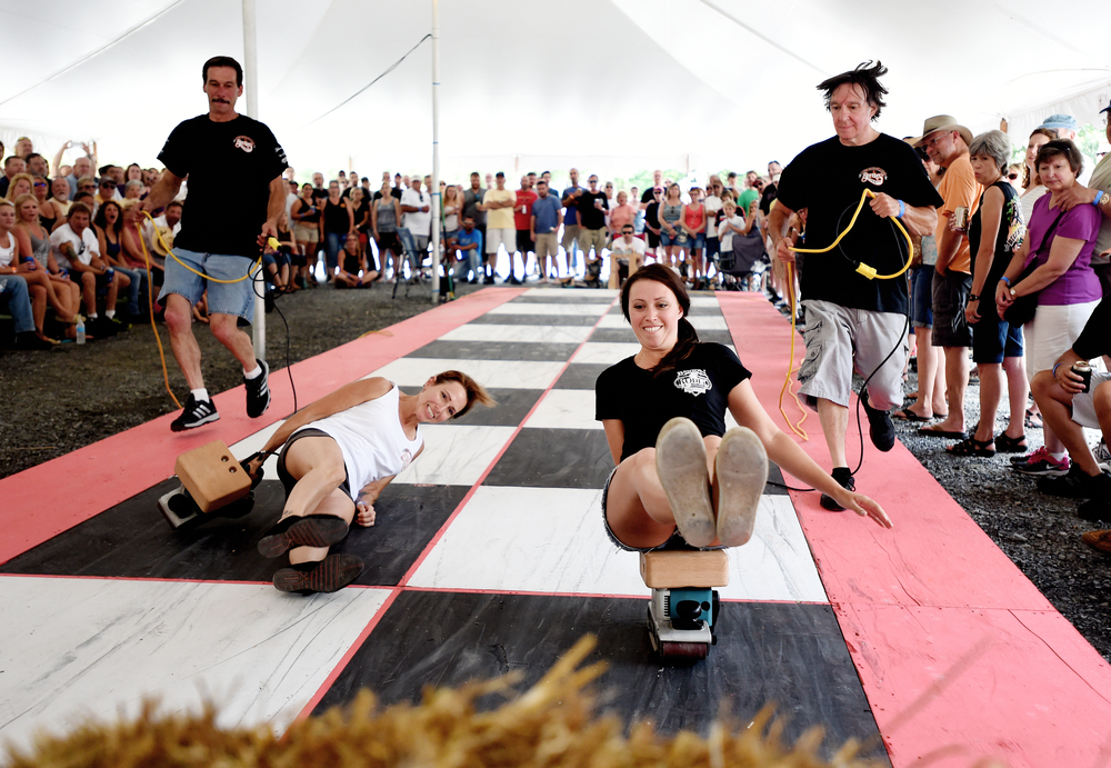 Joanna Blessings of Fleetwood (right) races down the track as Carol Benjamin of Oley falls off her sander at the 26th Annual Belt Sander Race at Bertie's Inn in Exeter Township on July 16, 2016. The race, the only one of its kind in the nation, benefits the National Multiple Sclerosis Society of Greater Delaware chapter. (Reading Eagle: Sarah Stier)