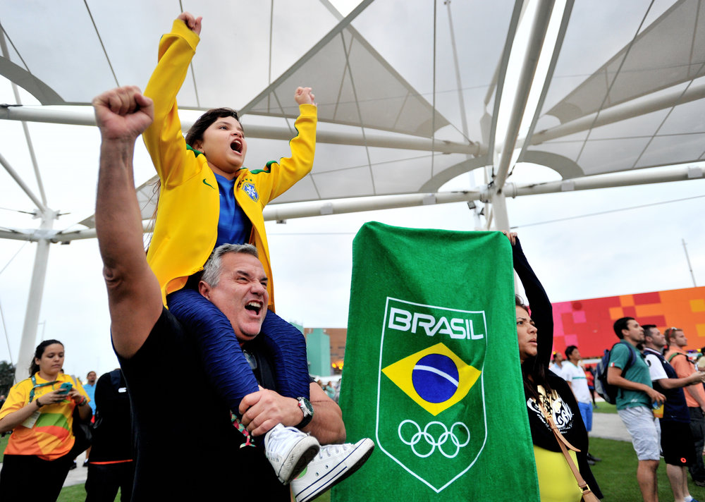 Olive Costa and his daughter Victoria, 7, cheer while his wife, Antomia Costa, holds up a Brazilian flag in support of a Brazilian judo player at the Olympic Park in Rio de Janeiro, Brazil, on August 8, 2016. (Sarah Stier | Ball State at the Games)