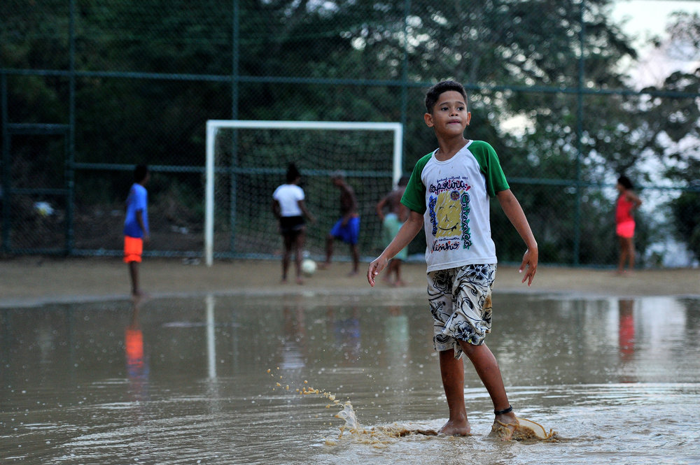 A child plays in a mud puddle while friends play soccer in the favela that they live in in Rio de Janeiro, Brazil, on August 12, 2016. (Sarah Stier | Ball State at the Games)