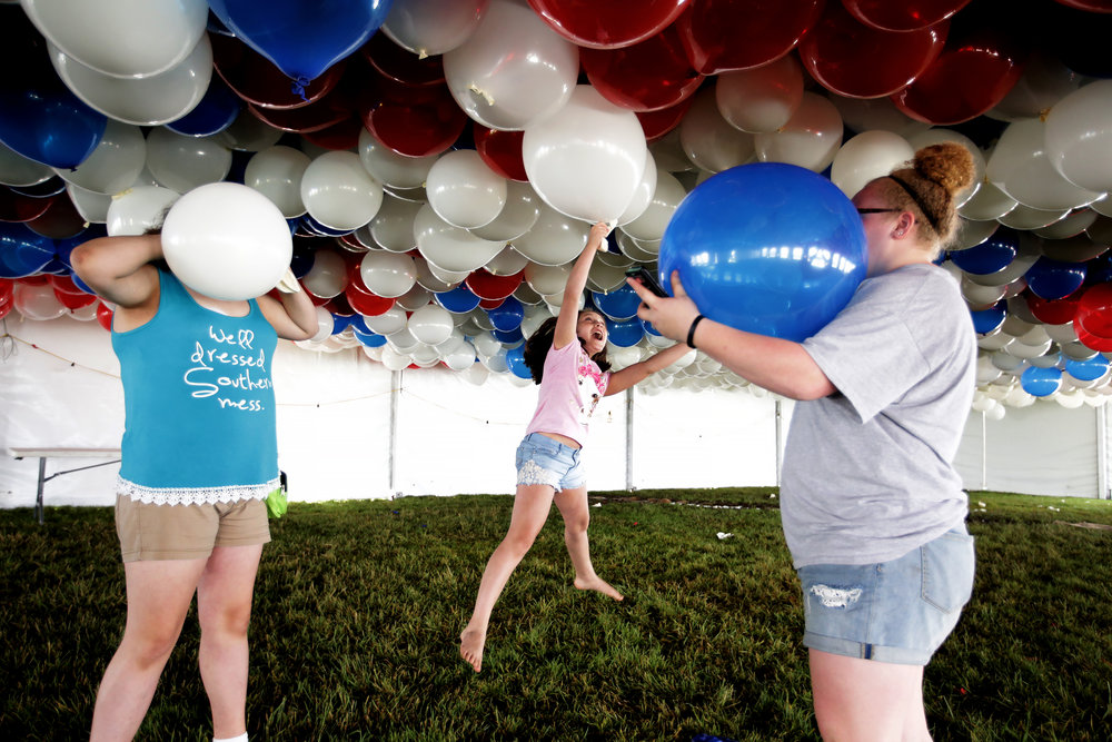 Makayla Stewart (left), 14, and Kaeleena Stewart (right), 14, blow up balloons while Kenadie Stewart, 10, of Terre Haute, Ind., reaches to grab one in the balloon tent at the 101st running of the Indianapolis 500 at Indianapolis Motor Speedway on Sunday, May 28, 2017.