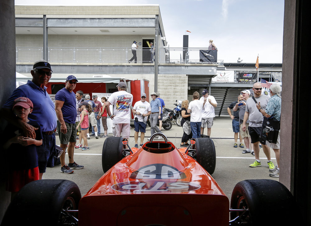 Fans take photos of cars in the garages at the SVRA Brickyard Vintage Race at Indianapolis Motor Speedway on Saturday, June 17, 2017.