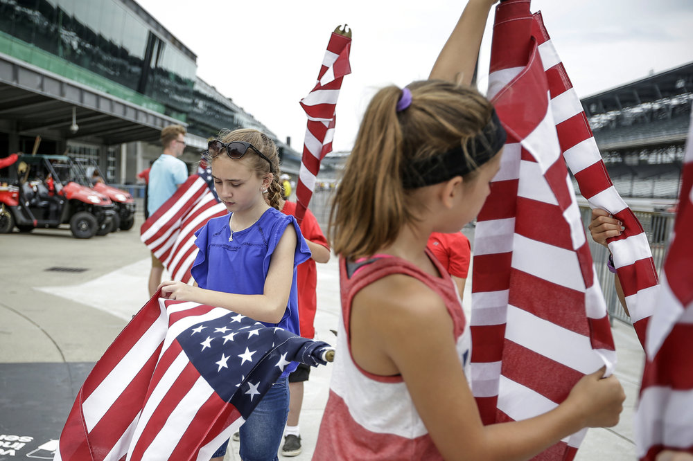 Ava Carter, 11, rolls her flag after ceremony for the National Anthem at the SVRA Brickyard Vintage Race at Indianapolis Motor Speedway on Saturday, June 17, 2017.