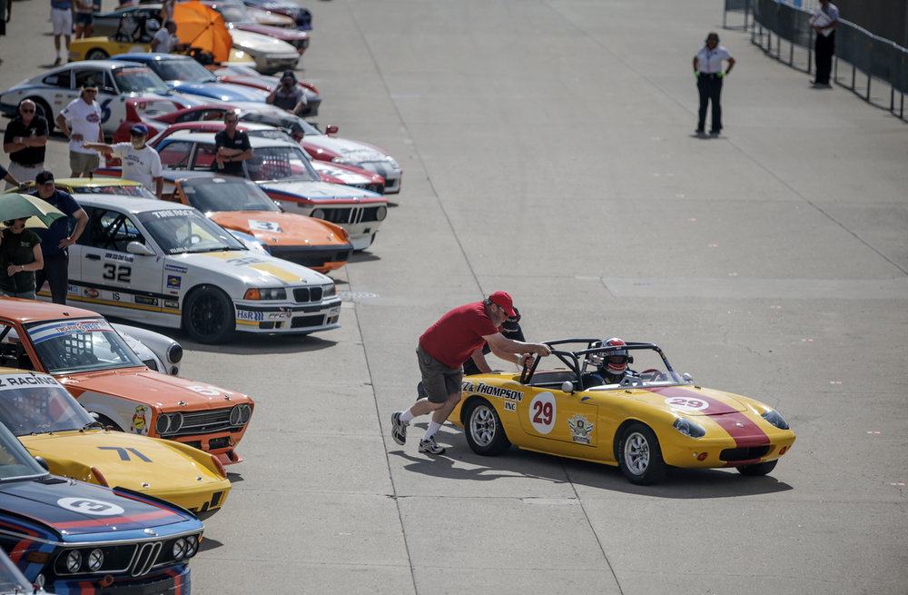 Crew members try to get a vintage car started prior to the start of a race at the SVRA Brickyard Vintage Race at Indianapolis Motor Speedway on Saturday, June 17, 2017.