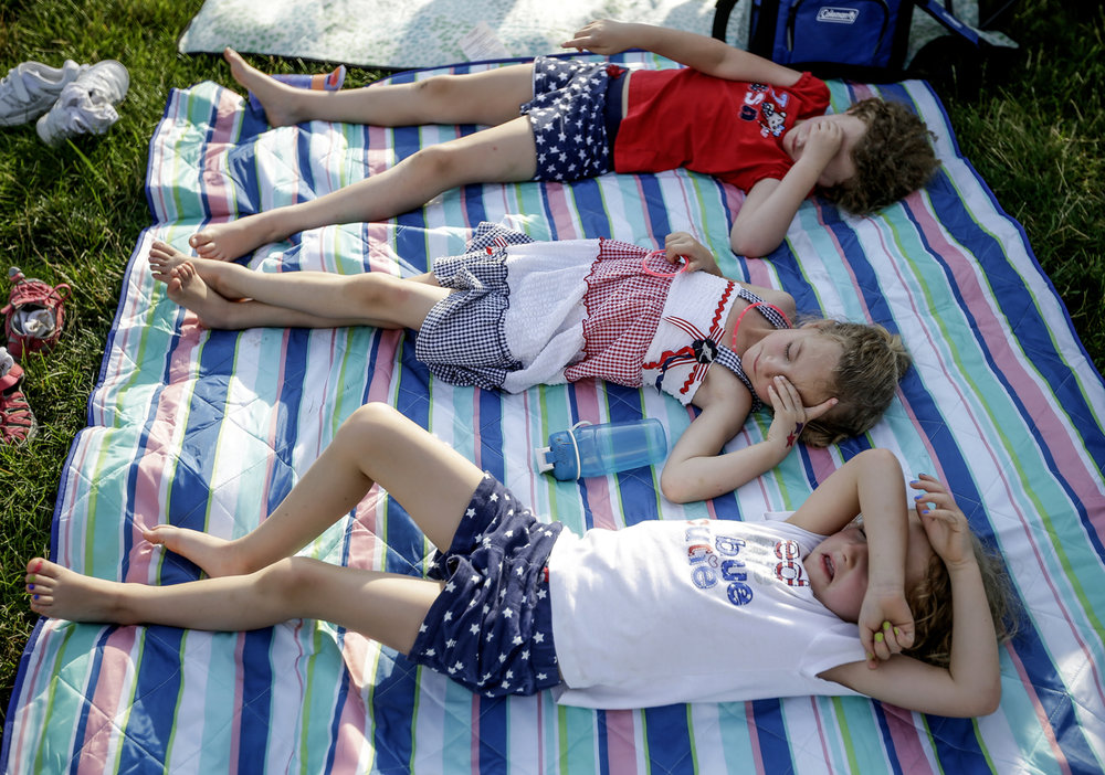 Charlotte McGuire (top), 7, and her sisters Nora (middle), 5, and Isabel, 5, listen to the music playing at the IPL Freedom Festival in downtown Indianapolis on Tuesday, July 4, 2017.
