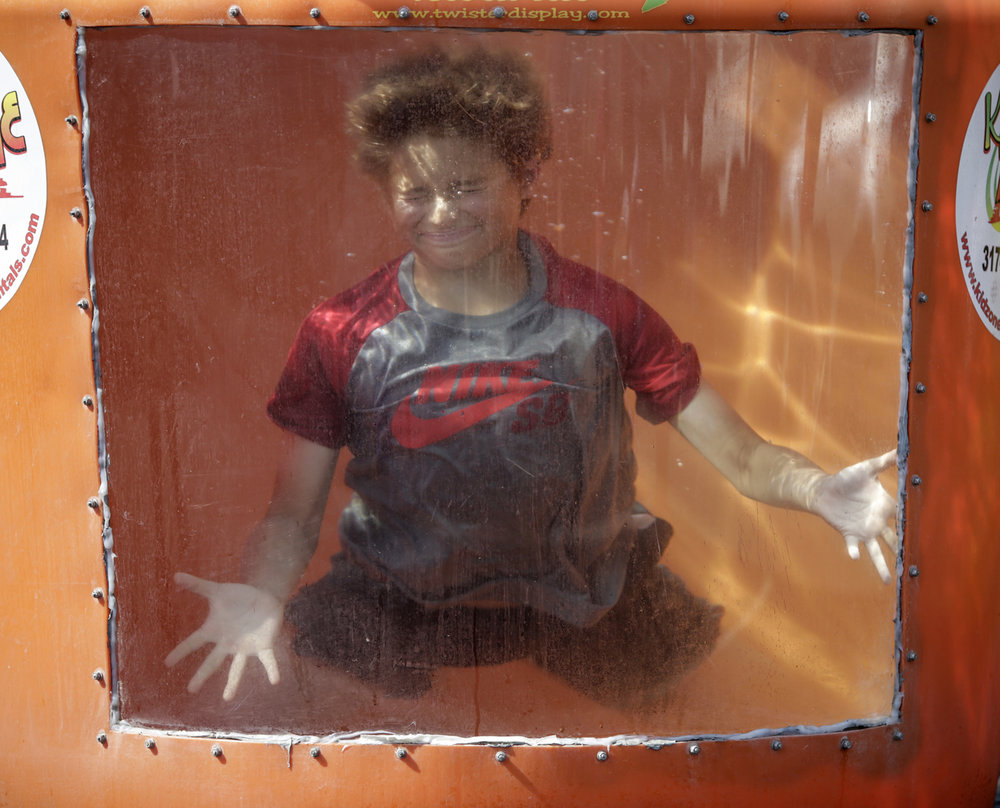 Henry Staser, 12, gets dunked in a tub of water at the Fourth of July ¡Ole! Festival at St. Mary's Church in Indianapolis on Tuesday, July 4, 2017.