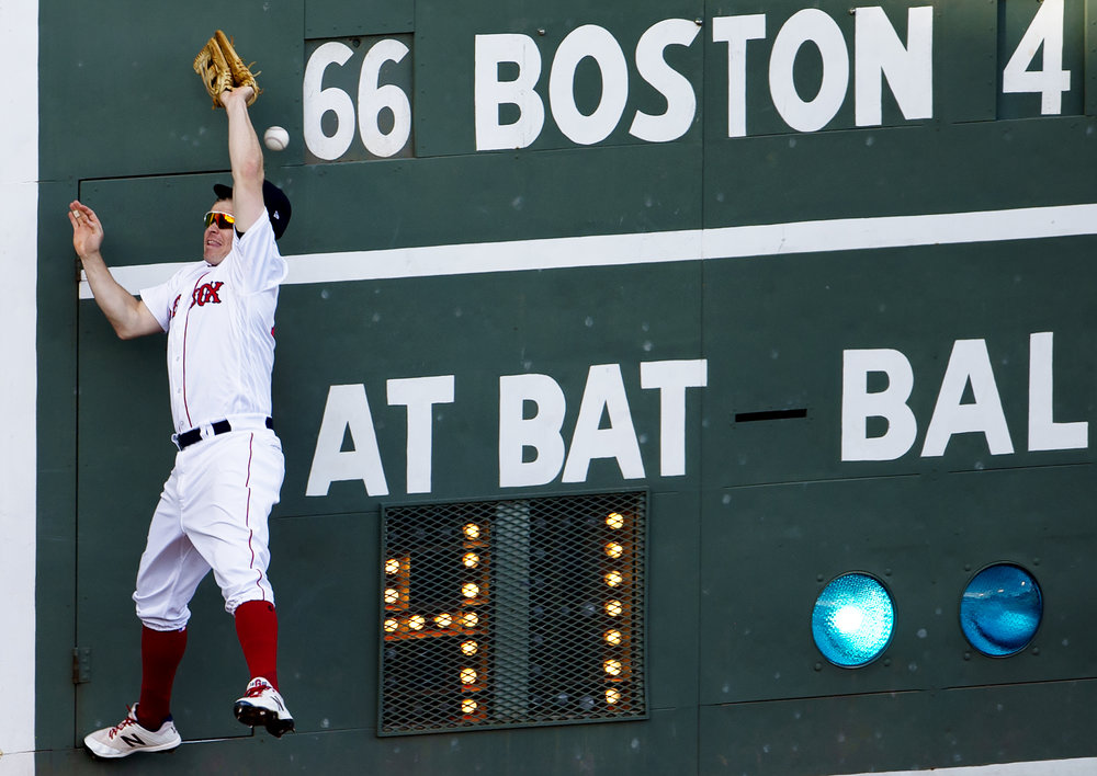 Boston Red Sox infielder Brock Holt collides with Fenway's fabled Green Monster during the game against the New York Yankees at Fenway Park in Boston, Massachusetts, on Sunday, September 30, 2018.