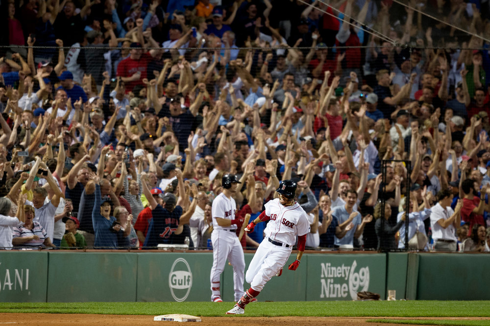 Boston Red Sox outfielder Mookie Betts rounds first base after hitting a grand slam during the game against the Toronto Blue Jays in Boston, Massachusetts on Thursday, July 12, 2018. The home run came after a 13-pitch at-bat.