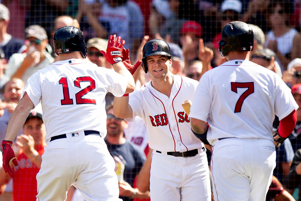 Boston Red Sox outfielder Brock Holt and catcher Christian Vasquez high-five outfielder Andrew Benintendi during the game against New York Mets at Fenway Park in Boston, Massachusetts, on Sunday, September 16, 2018.