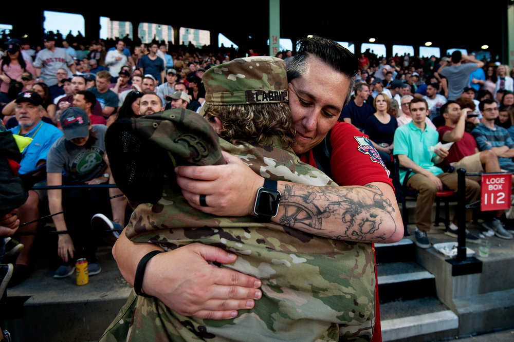 A fan hugs a servicewoman who was honored during Fenway's Hats Off to Heroes ceremony in the fourth inning of the game against the Chicago White Sox in Boston, Massachusetts on Friday, June 8, 2018.