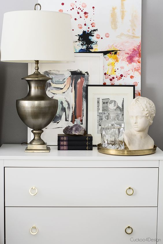 I bet you guys already have it down by now and don't need me to point it out. But, here we see a balanced nightstand through the use of a vertical lamp and art, horizontal books and gold tray, and sculptural bust and geode! The layered art also adds a nice dimensional touch to the vignette. Love it!