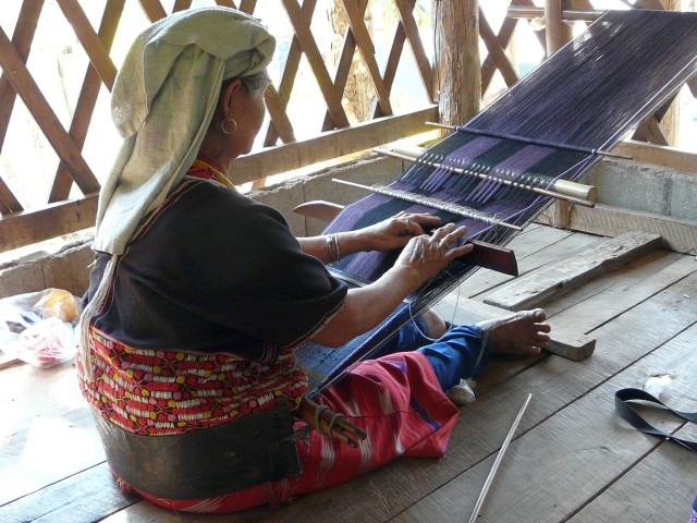Keren woman in Northern Thailand weaving with a back strap loom.