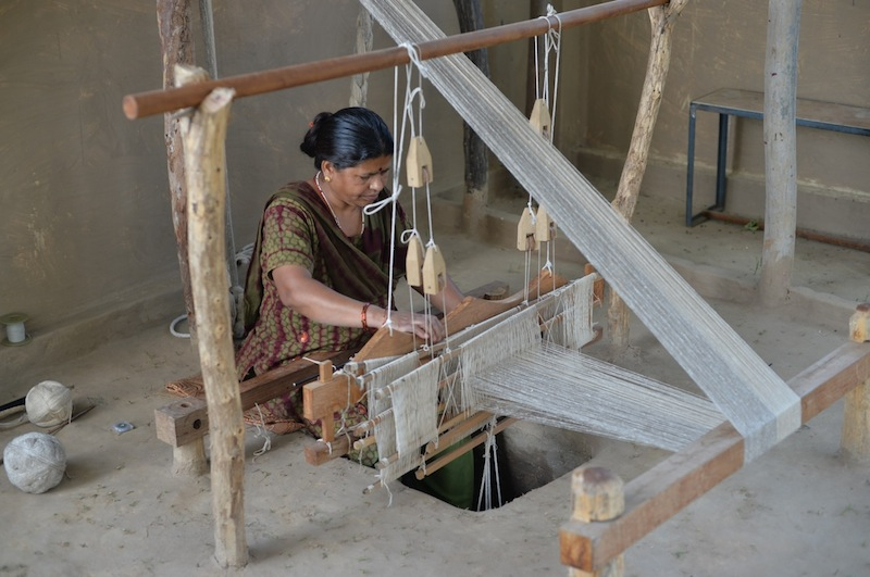 Indian woman using a pit loom. Photo credit to Ganga Studio blog.