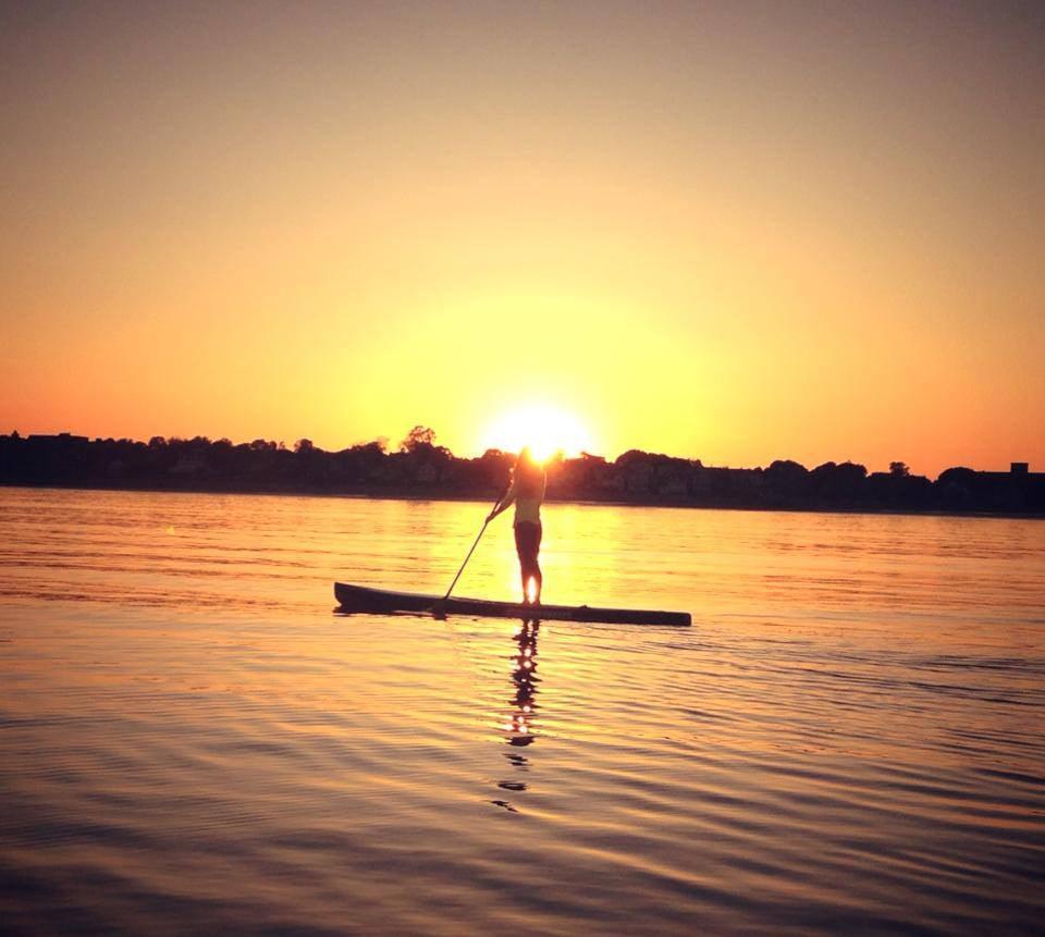 paddleboarding into sunset