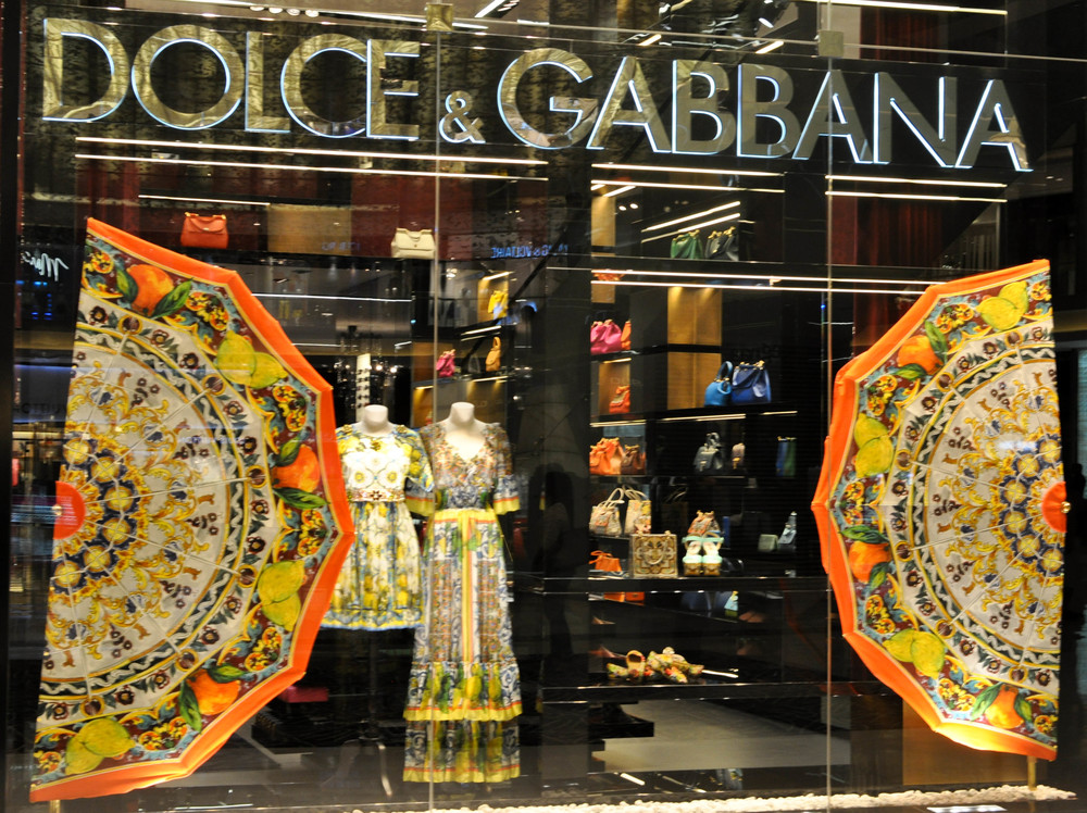 DOLCE & GABBANA    Two large bright, fruity fabric, umbrella halves framed the scene for Dolce & Gabbana's late summer collection of clothes and accessories creating a bold, feminine and sophisticated impression.