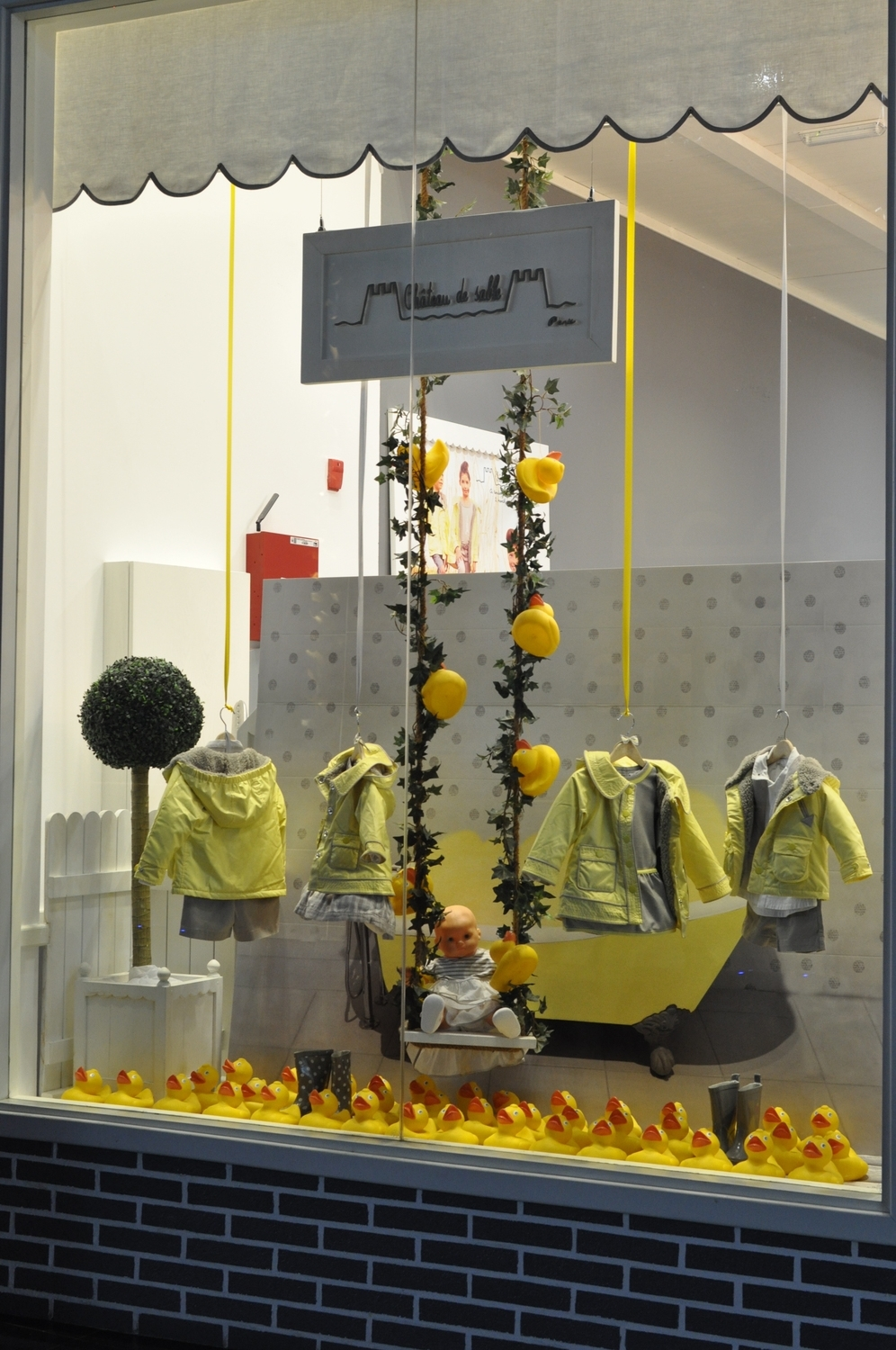 CHATEAU DE SABLE    A yellow rubber duck theme depicting a bathroom scene with raindrops was bright and eye-catching.   The colour combination of yellow and grey allowed for a gender-neutral display of their Autumn/Winter raincoats and gumboots.