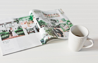 Image of a magazine spread out with a cup of coffee on the side.  The coffee mug is white with beading around the top.  The magazine is The Celebration Society Magazine.  This picture leads to the published work of Debra Eby, Jacksonville Fine Art photographer.