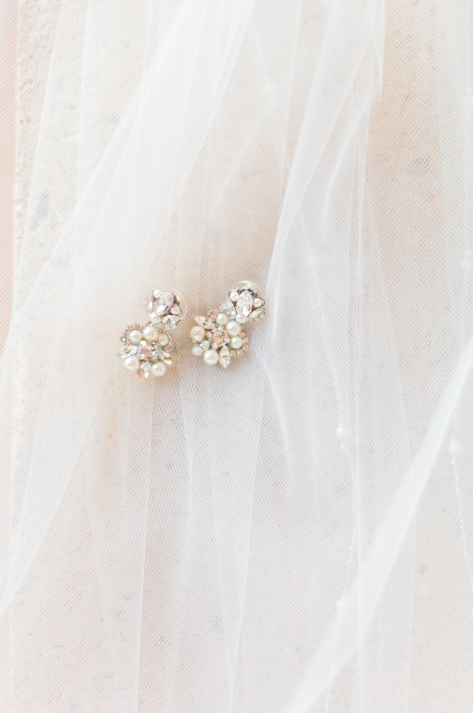 Image of diamond earrings laying on a bridal veil at TPC Sawgrass in Ponte Vedra, Florida