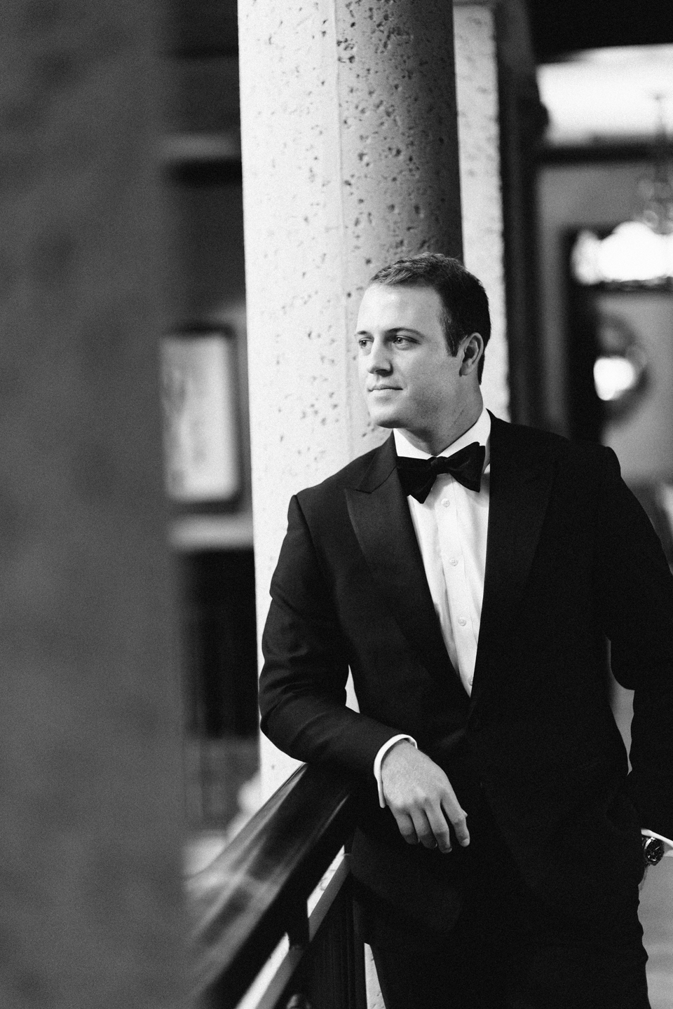 Image of a black and white portrait of a groom on his wedding day.  The groom is wearing a black tuxedo and leaning on the railing at the TPC Sawgrass in Ponte Vedra, Florida