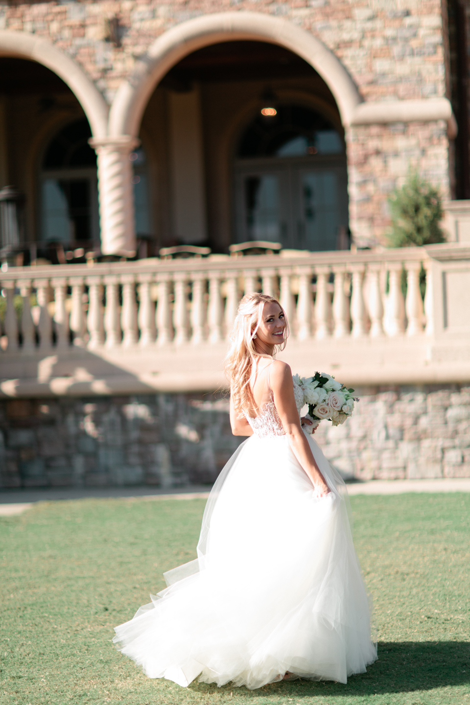 Picture of a bride in her Calvet Couture wedding gown twirling in front of TPC Sawgrass in Ponte Vedra, Florida