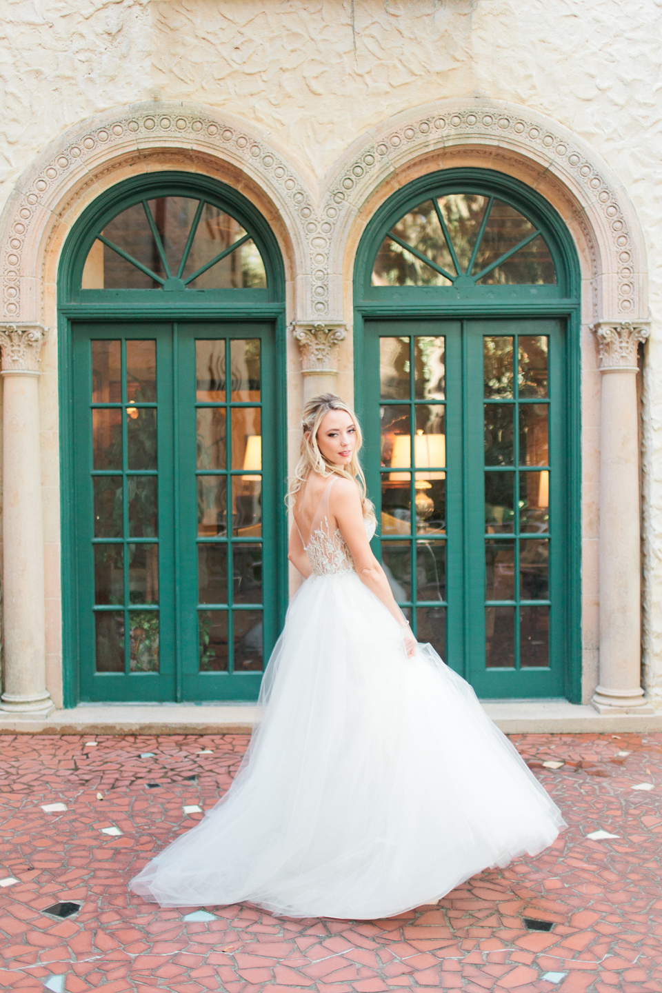 Image of a bride twirling in her Calvet Couture wedding gown in front of the Epping Forest Yacht Club in Jacksonville, Florida
