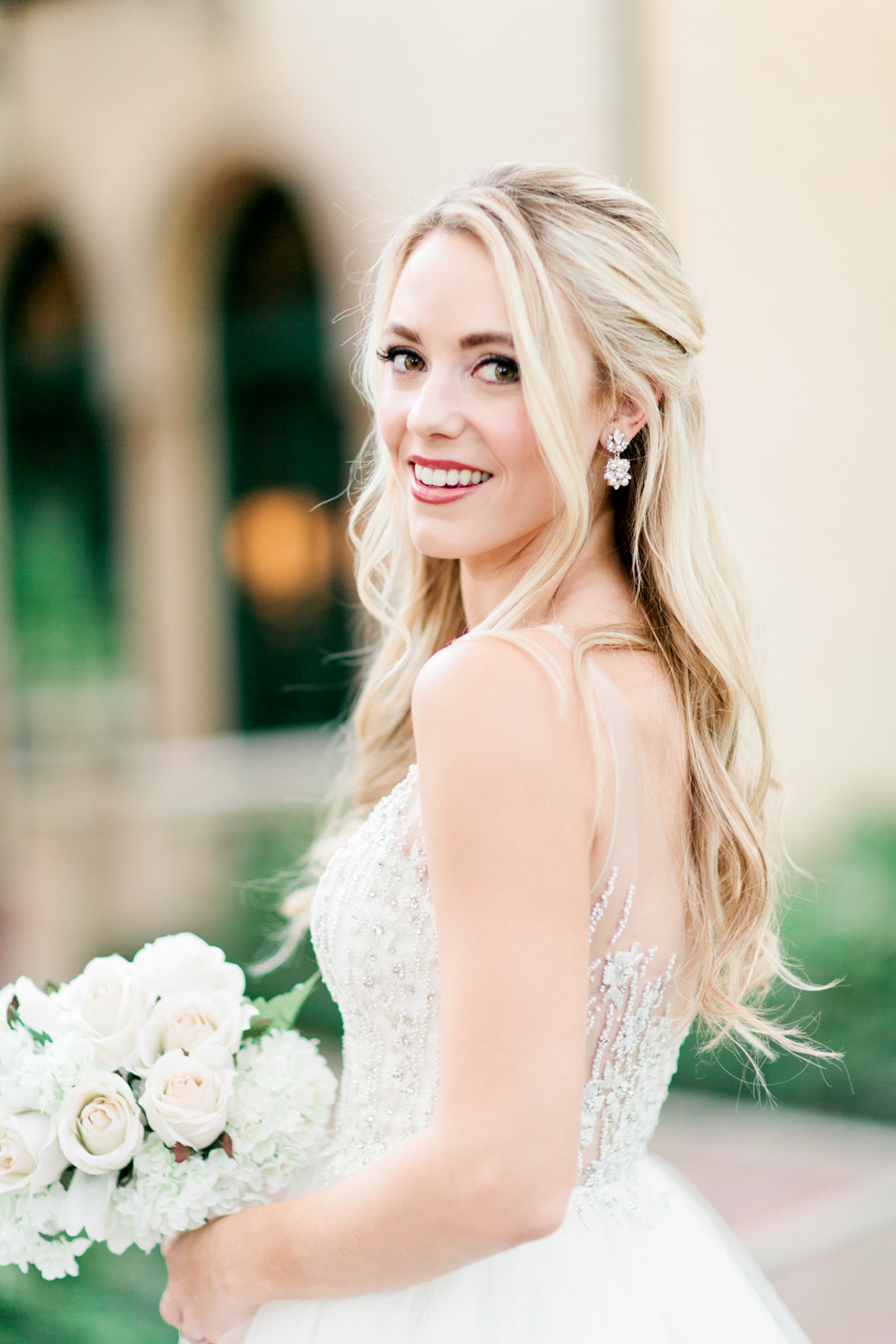 Picture of a close up of a bride in a wedding gown by Calvet Couture Bridal.  The bride is in front of Epping Forest Yacht Club in Jacksonville, Florida.