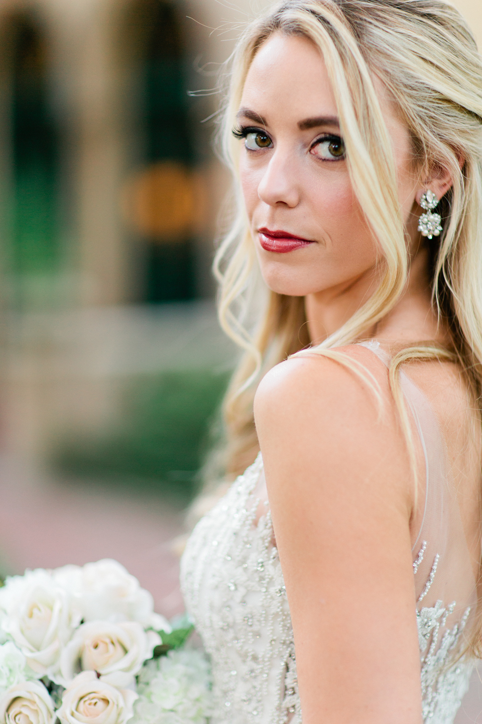 Image of a bride in a wedding gown, glancing over her shoulder.  Her hair is long and curled.  She is standing in front of the Epping Forest Yacht Club in Jacksonville, Florida