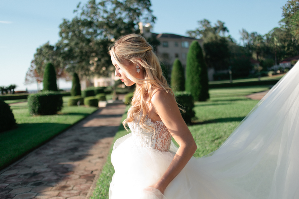 Picture of a bride walking and holding her Calvet Couture bridal gown.  She has long curls and is at the Epping Forest Yacht Club in Jacksonville, Florida