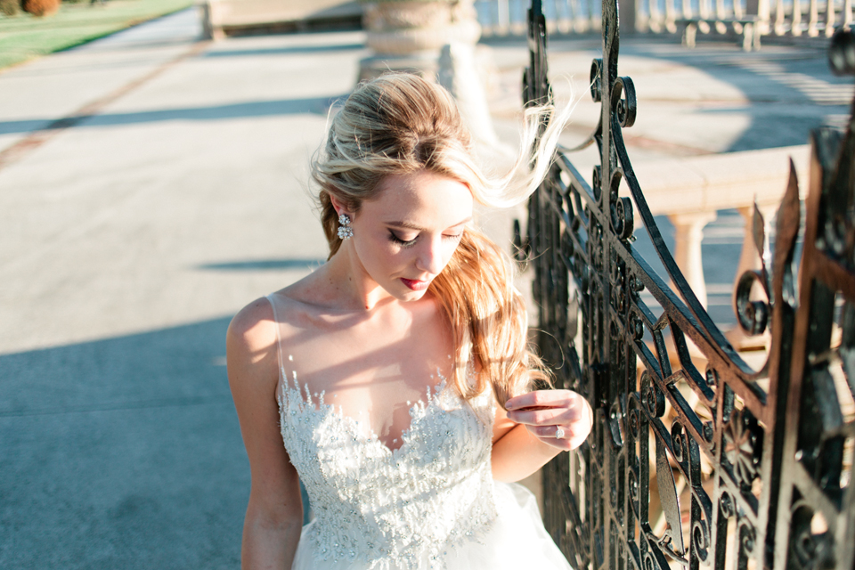 Image of a bride at an iron gate, glancing down at the Epping Forest Yacht Club in Jacksonville, Florida