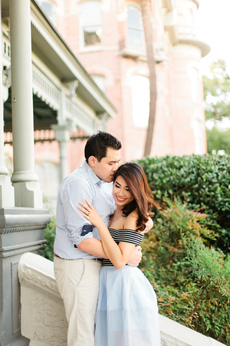 Image of engagement portraits on the steps of the Henry B Plant museum in Tampa, Florida.  The couple is in a romantic embrace.