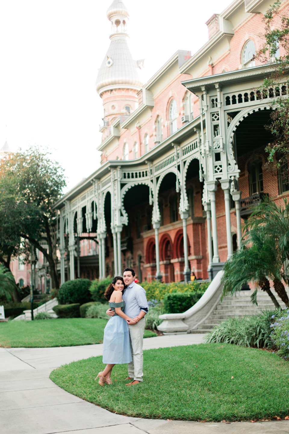 Image of an engaged couple embracing in front of the Henry B. Plant museum in Tampa, Florida.