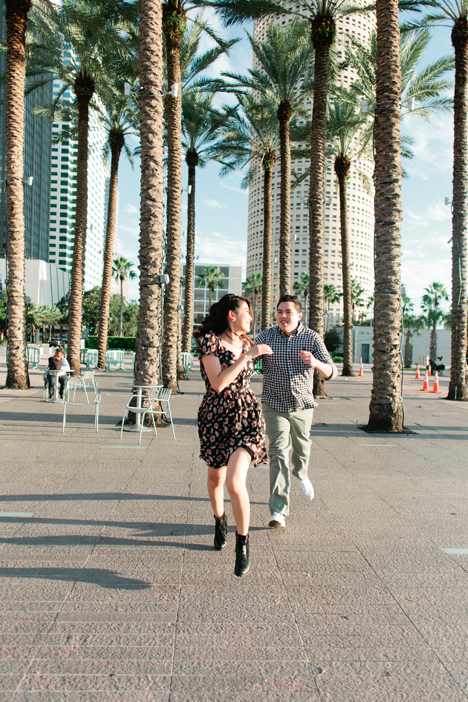 Image of an engaged couple running playfully at Curtis Hixon Waterfront Park.