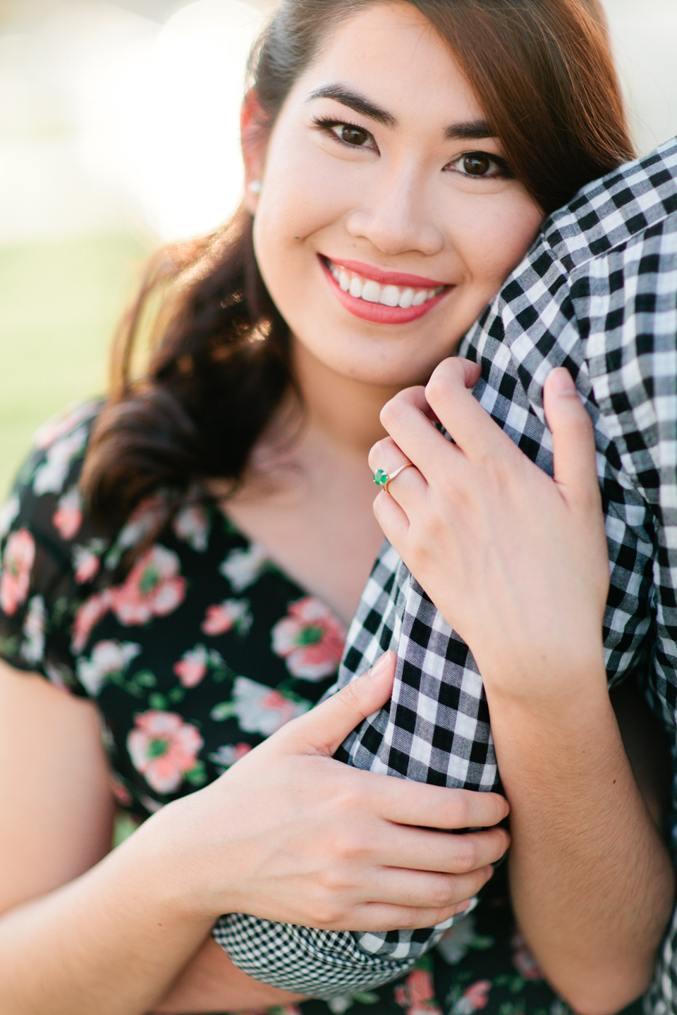 Image of a beautiful woman smiling while holding the arm of her fiance.  This engaged couple is at Curtis Hixon Waterfront Park in downtown Tampa, Florida.