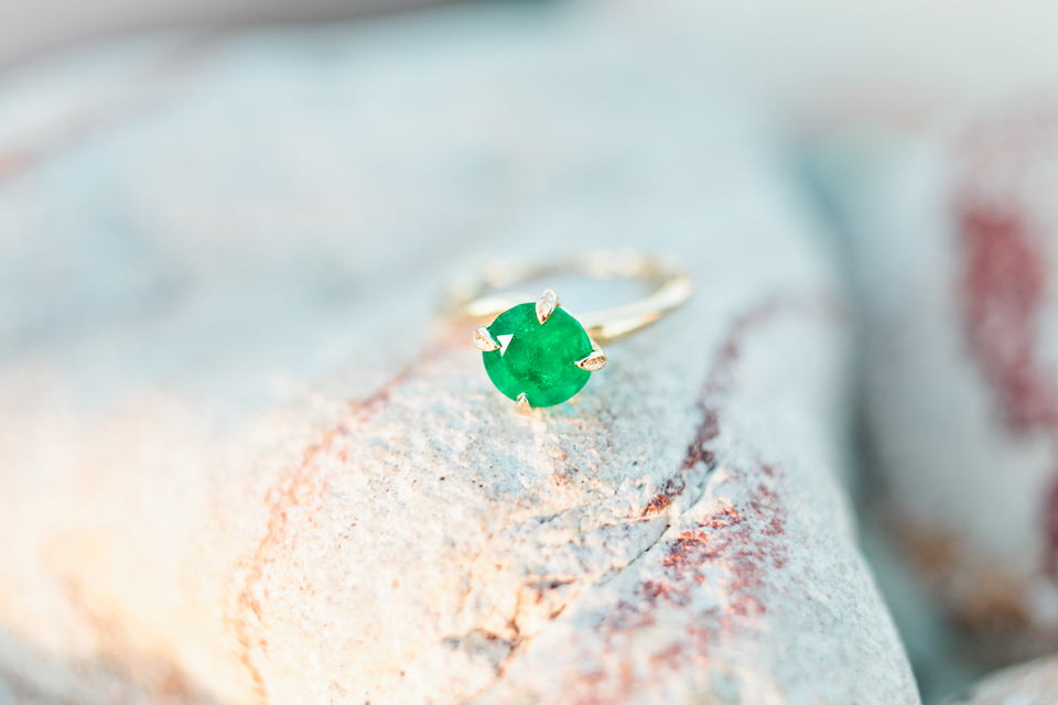 Image of a beautiful emerald engagement ring sitting on top of a smooth stone.  This is at Curtis Hixon Waterfront Park in downtown Tampa, Florida.