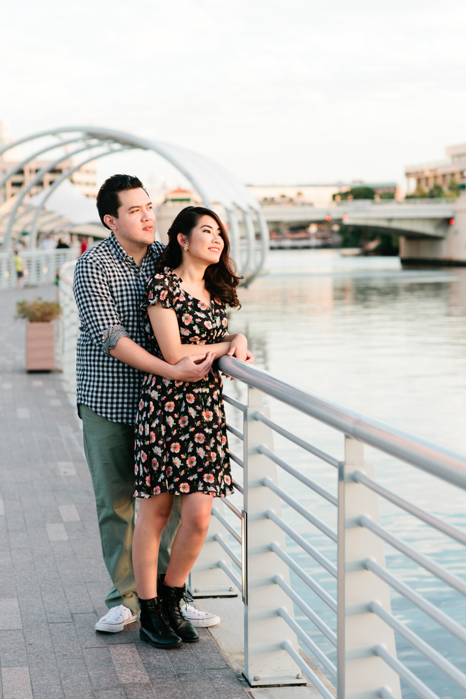Image of an engaged couple looking out on the riverwalk in downtown Tampa at Curtis Hixon Waterfront Park.
