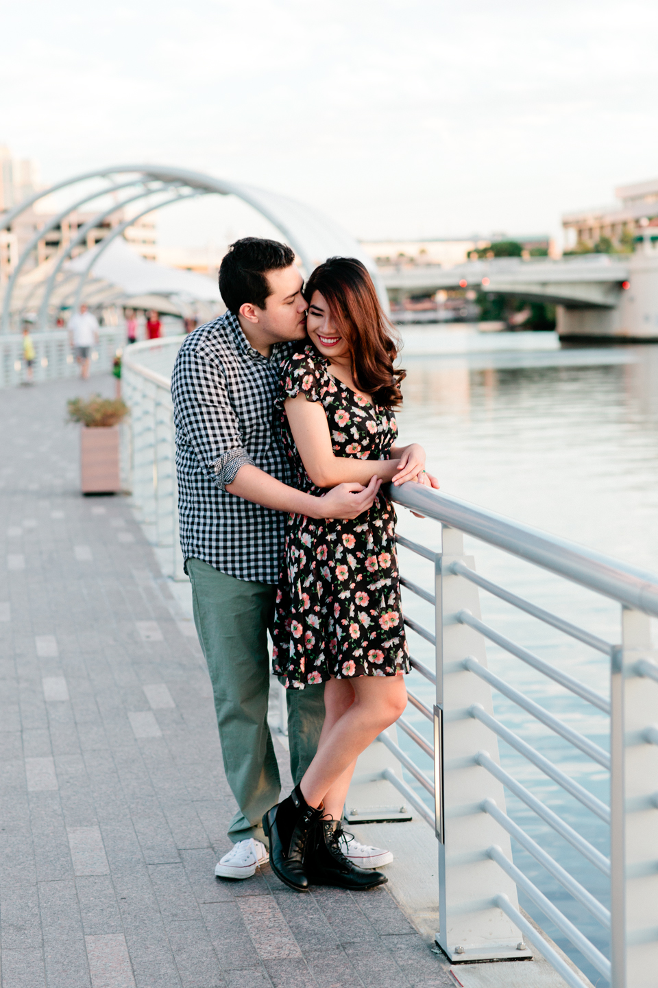 Picture of an engaged couple embracing on the Tampa Riverwalk in downtown Tampa at Curtis Hixon Waterfront Park.